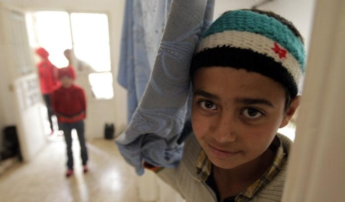 A Syrian boy who fled the violence in Syria wears a headband in the colours of the pre-Baath Syrian flag as he stands in a shelter housing refugees in the Lebanese city of Arsal in the Bekaa Valley on March 26, 2012. UN-Arab League envoy Kofi Annan said that only Syrians could determine President Bashar-al-Assad's fate and called for the rival sides to negotiate an end to the conflict. AFP PHOTO/JOSEPH EID (Photo credit should read JOSEPH EID/AFP/Getty Images)