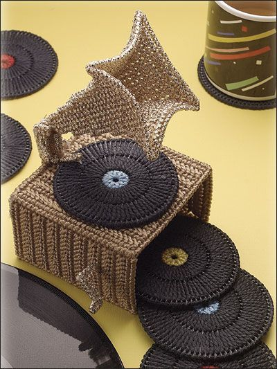 """A whimsical old-time charmer, this phonograph coaster holder with record coasters would make an eye-catching conversation piece. This e-pattern was originally published in Coaster Sets. Size: Coaster: 3 5/8"""" (9.2cm) diameter. Holder: 4"""" x 6 1/2"""" x 5"""" (10.cm x 16.5cm x 12.7cm). Made with plastic canvas craft cord, plastic canvas yarn, 7-count plastic canvas and 4 1/2"""" (11.4cm) plastic canvas circles. Skill Level: Experienced"""