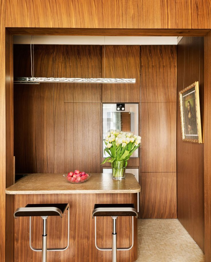 The compact kitchen is a lesson in smart space planning. A Gaggenau oven and wine cooler are integrated into the wall, while the Gaggenau refrigerator is concealed behind the walnut paneling. Stools by Shin & Tomoko Azumi are pulled up to the countertop of Travertino Noce marble; the ceiling light is by Flos, and the photograph is by Tadao Cern.