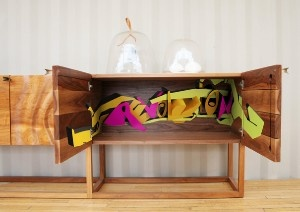 """Combining sleek modern furniture, with energetic and wild graffiti, designer Ilan Dei has the makings of a visionary. His three pieces – """"Namibia"""" Credenza, Side-Table, and Console all look normal to the first glance. However, upon closer inspection they show their true Hip-Hop colors"""