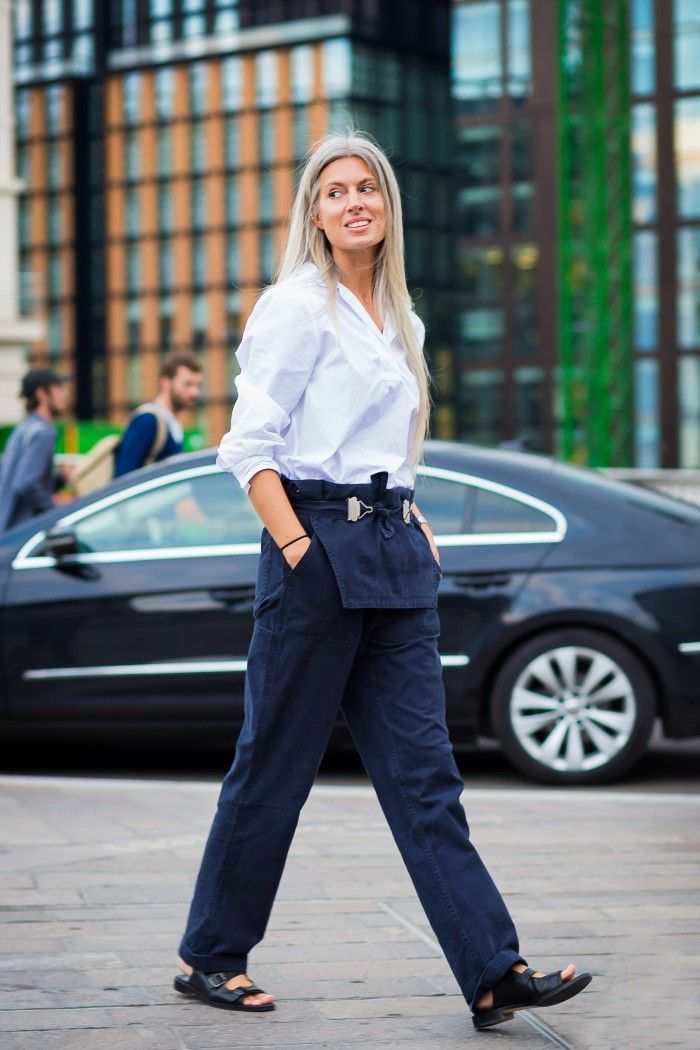 A white shirt is worn with navy overalls and black sandals.