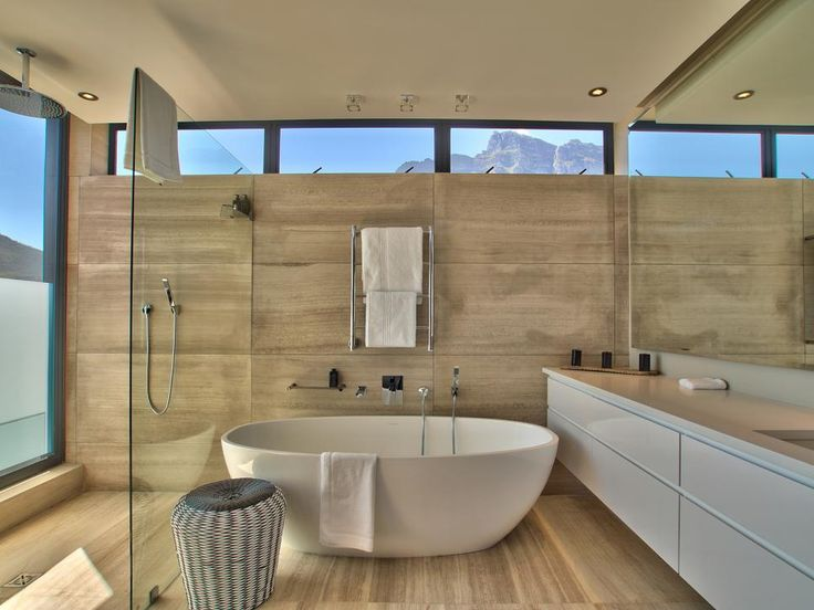 a freestanding slipper tub provides an elegant place to soak and enjoy the view of the - Bathroom Tile Ideas South Africa