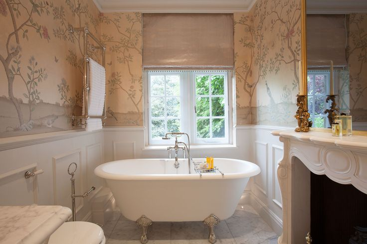 En-suite bathroom with traditional freestanding bath and bespoke TV mirror above fireplace inspired by Louis XV era | JHR Interiors