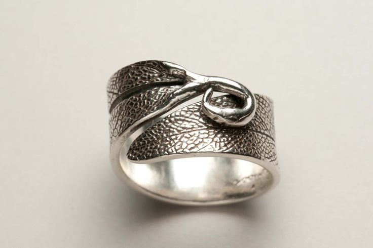 Adjustable metal clay ring. This would be neat with a gem in the curl of the leaf stem.