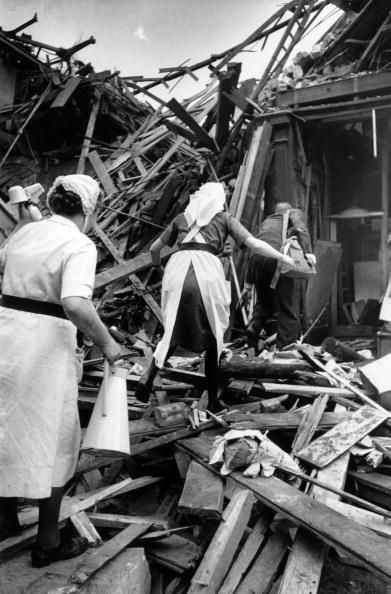 Nurses climb through the rubble at Farringdon Market London after a rocket had fallen on it during the last months of WW II.