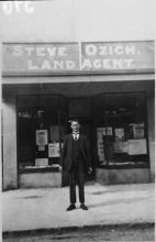Steve Ozich outside his Land Agents shop 1926. Land agent, taxi-driver, billiard hall proprietor. Started the Henderson Bowling Club. Long-lived owner of Falls Hotel when it was sited near the railway line, now Stevie's Lane. More at http://www.localhistoryonline.org.nz/cgi-bin/PUI?e=0--------0-----------0-1-0-0-&a=d&c=supercol&cl=CL30.All.Ozich,%20Steve%20(interviewee)&d=waoh-WOH-1042