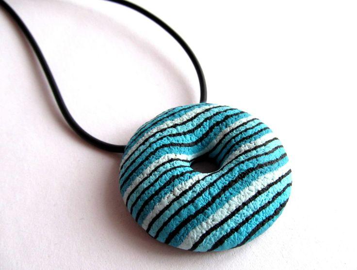 Tyrkysové proužky Dutý donut z polymerové hmoty . Přívěsek je navlečen na pryžové bužírce ukončené zapínáním ( karabinka) . Velikost přívěsku je cca 5 cm . Délka návleku je cca 45 cm + 5 cm adjustační řetízek .
