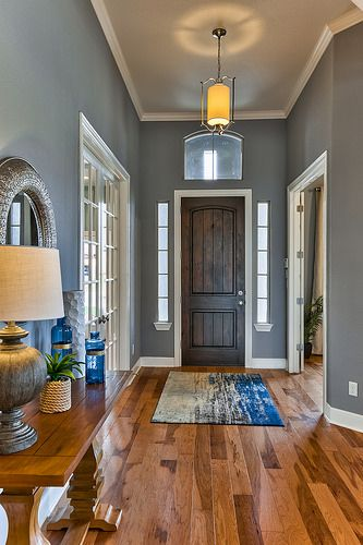 Fall in love with this entry/foyer! The variations in the hardwood floors pair well with the grayish blue walls and the accents of blue in the home decor. Click to view more of these new homes in Woodford Estates. | MileStone Community Builders