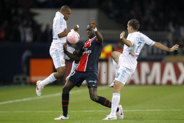 Paris St Germain's Mohamed Sissoko (C) challenges Marseille's Andre Ayew (L) and Benoit Cheyrou (R) during their French Ligue 1 soccer match at Parc des Princes stadium in Paris April 8, 2012.