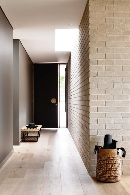 Mid-century modern. Light tan stone, grey walls, black door