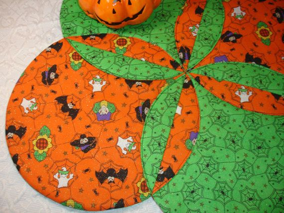 Halloween Table Top Runner Quilt and Centerpiece in bright orange, green and black featuring bats, witches, ghosts and other assorted Halloween characters, highlighted with gold sparkles. Use as a table centerpiece for a plate of cupcakes, cookies or to place your bowl of Halloween candy. Sure to brighten up any spot! Measures 20 1/2 x 20 1/2 or 24 diagonally. Last photo shows reverse side. Spot clean with cold water. Lay flat to dry. Iron, as needed. Thermore Batting quilt...