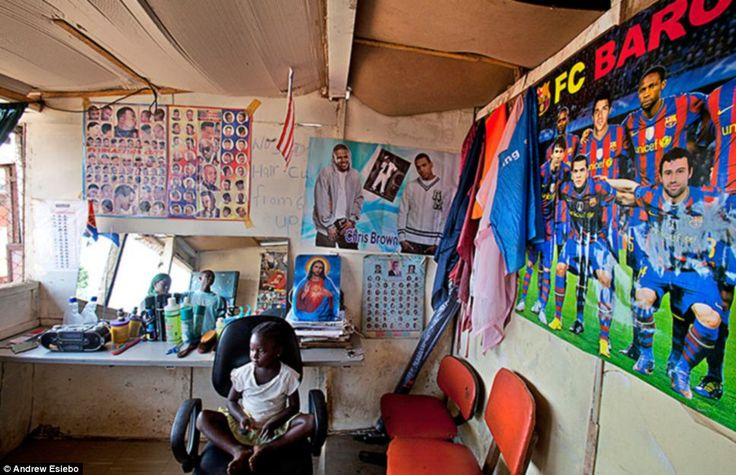 Family affair: The barber in this shop in Liberia has brought his daughter to work and she makes the most of the lack of customers by relaxing in the chair