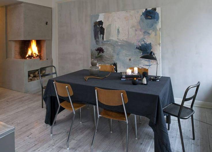 TRIVSELSSONE: Spisebordet ligger inntil en kjøkkenøy, med peis på den ene siden og et stortvindu mot bakgården på den andre. Det store maleriet er signert Peter Skovgaard. Trestolene er kjøpt i bruktbutikk. Bordlampen er klassikeren Kaiser Idell fra 1920-tallet.