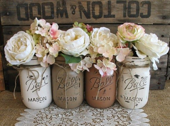 These painted mason jars filled with neutral blooms would serve as great decorations at a rustic chic wedding