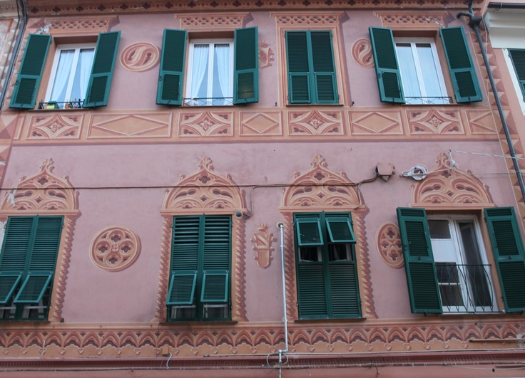 Typical Ligurian red historical building in Loano with green shutters and trompe l'oeil decorations.
