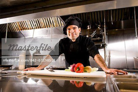 Portrait of Cuban chef standing in restaurant kitchen with cutting board and vegetables Stock Photo - Rights-Managed, Image code: 842-03198518
