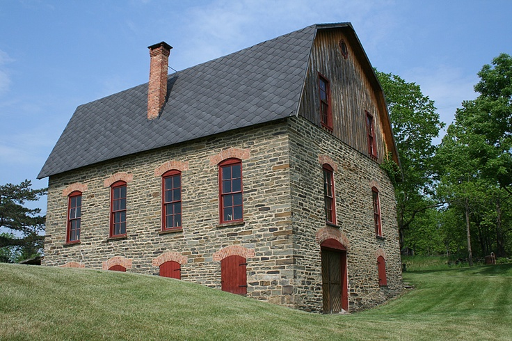 On the National Register of Historic Places, this stone barn is part of the Sherman Williams House and Fruit Farm located on State Route 54A in Bluff Point, New York (Yates County). Although the property is no longer a working fruit farm, this well-maintained post-and-beam barn was once used for grape storage.