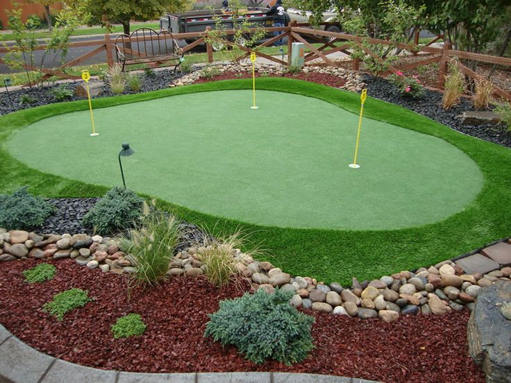 mini-size putting green with yellow signs surrounded by green grass carpet and some plant ornaments and river rocks feature wood fence system for golf yard