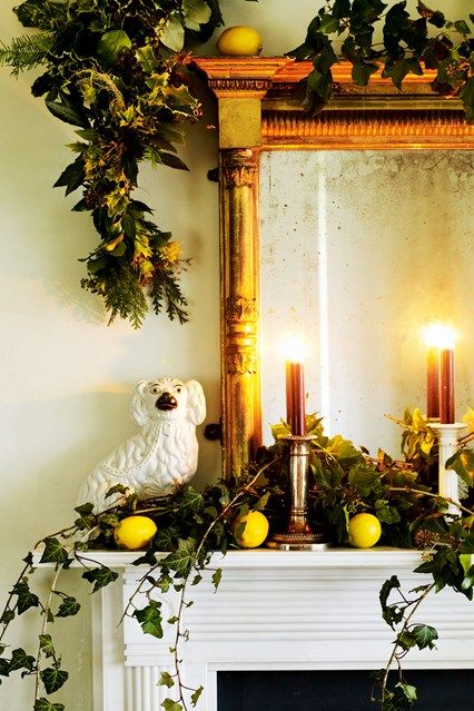 Antique candlesticks holding dark brown candles, and lemons - an original and inexpensive Christmas decoration that provides a zingy contrast to the greenery - deck the mantlepiece of designer Ben Penthreath.