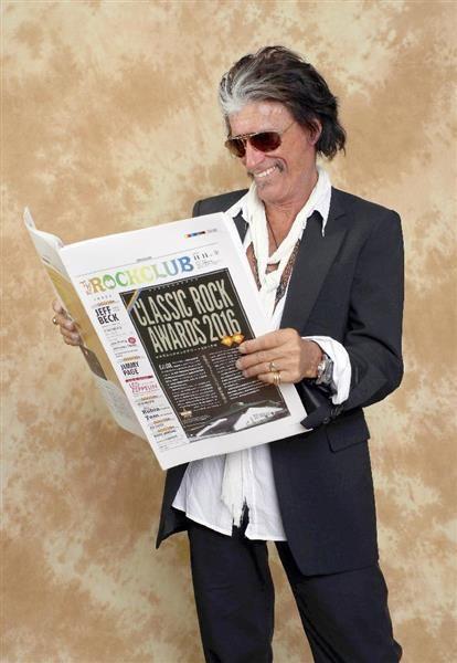 「クラシックロックアワード2016+ライヴパフォーマンス」会場限定のプレミアムタブロイド「ザ・ロッククラブ」の見本を手に取るジョー・ペリー(エアロスミス)