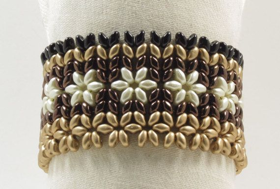 A stunning bracelet beaded with SuperDuos in a beautiful floral design. 4 different color SuperDuos have been beaded together to depict a mass of tiny flowers. Earth tone colors of matte metallic gold, pearl coat cream, dark bronze, and black. Very stylish. Great for everyday or for a night out. The clasp is a vintage style antique bronze plated brass box clasp. It is lead free and nickel free. When its clasped it measures 7 around and is 1 1/2 wide.  Design by Akkesieraden…