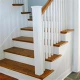 Graceful staircase with quarter-sawn oak treads and white trim ...
