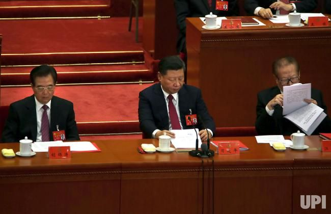 China's President Xi Jinping (C ) and former Presidents Jiang Zemin (R ) and Hu Jintao review documents during the closing ceremony of the…