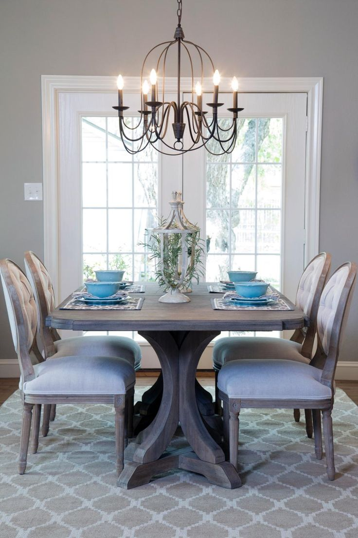 French country gray dining room - The Dining Room Is Illuminated With A Dark Metal Chandelier And Staged With Bright Comfortable