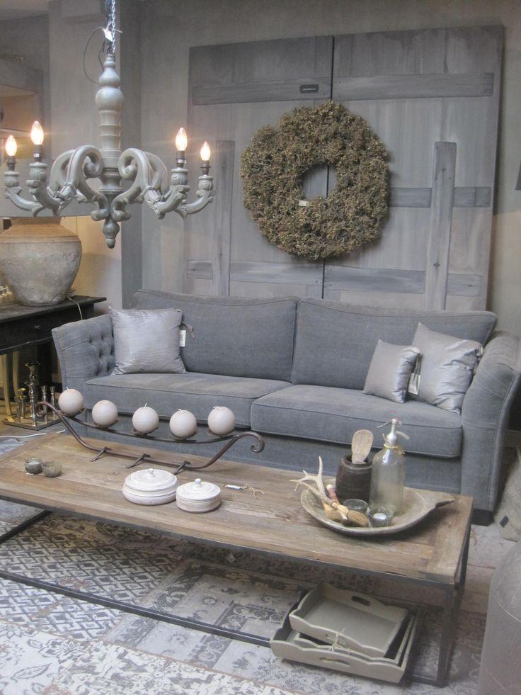 Grijze 3-zits bank van spijkerstof en langwerpige industriële salontafel op een patchwork kleed. Kandelaar met bolkaarsen en dienblad met spuitfles en accessoires van Hoffz.