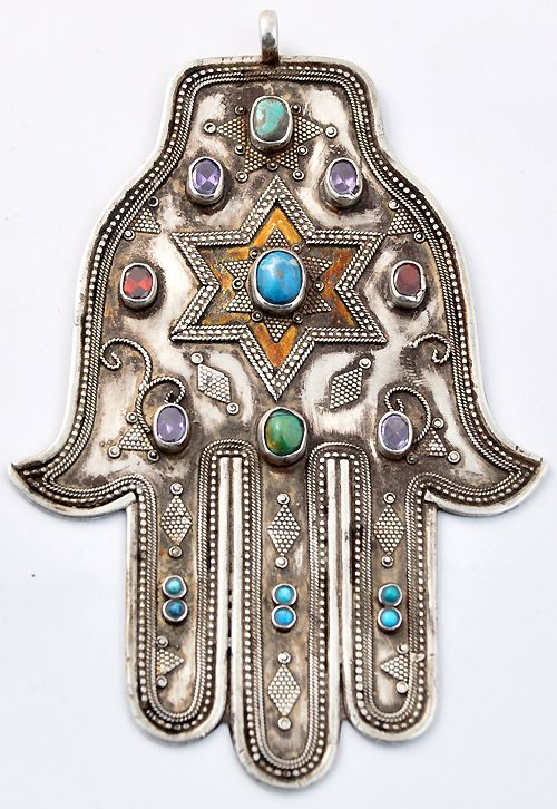 """Hamsa. A hamsa is an amulet shaped like a hand, with three extended fingers in the middle and a curved thumb or pinky finger on either side. It is thought to protect against the """"evil eye"""" and is a popular motif in both Jewish and Middle Eastern jewelry."""