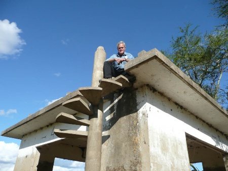 Scott Pelley (CBS 60 Minutes) sitting on top of the historic Lion House in Gorongosa National Park (Mozambique)
