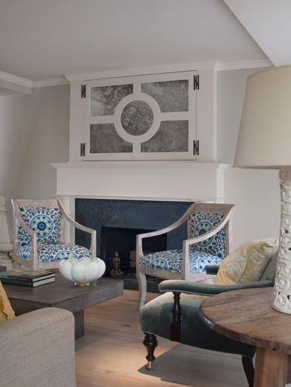traditional living room by Heydt Designs.  Mirrored doors hide a tv over the fireplace.