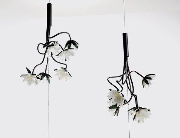 Lampara Glamour flores blancas.  Lámpara Glamour. Un ramo de flores blancas cuelgan de un hilo como suspendidas en el aire. De una base cilíndrica situada en el suelo sube un cable de acero donde se sujetan las flores. La base proyecta luz a las flores, creando un juego de luces y sombras que se proyectan al techo. Una lámpara decorativa llena de fantasía. Altura mínima de 50cm y máxima de 400cm.  http://es.ideesdisseny.com/eshop/illuminacio/sostre/lampada-glamour-flors-blanques-id-366.htm