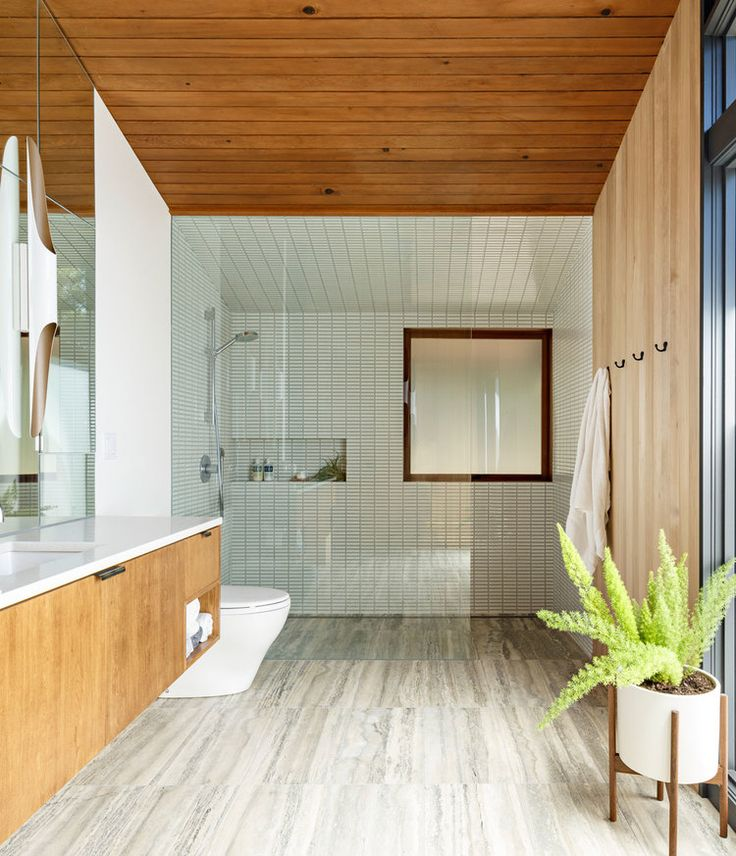 Midcentury modern bathroom design: soft blue tile, paneled wood ceiling, modernica case study planter, floating wood vanity