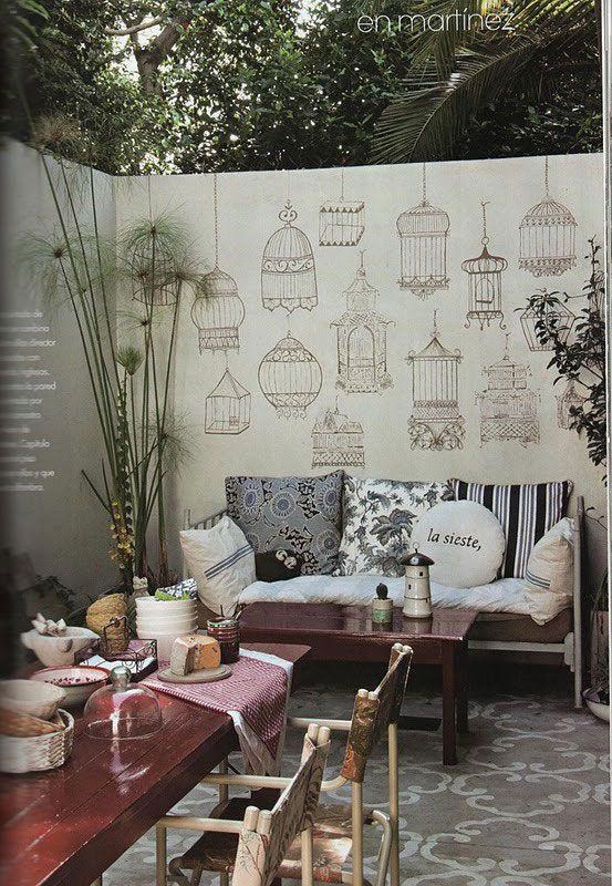 Bringing the indoors out. This is a patio space. Loving the stenciled birdcage pattern on that concrete wall.