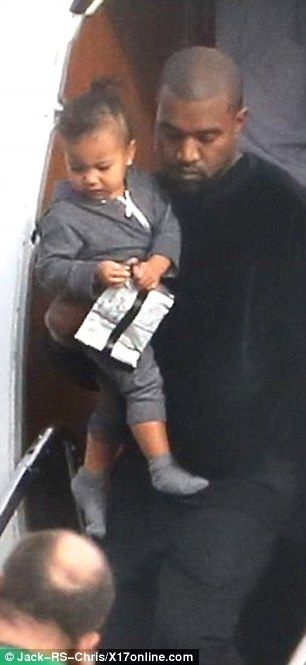 Doting daddy: Kanye West carried daughter North as he and wife Kim Kardashian arrived in California on Sunday after spending nearly a month apart on business commitments