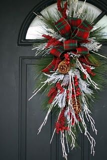 For the front door. SFH adds:Amazing what a bunch of white sticks can do in an arrangement like this. Wonderful against the gray door.