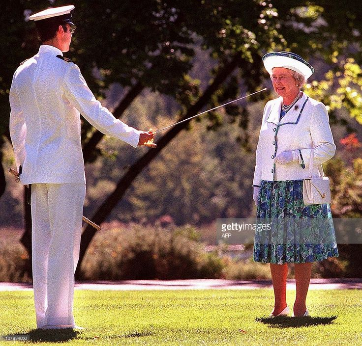 Britain's Queen Elizabeth II (R) is introduced to the Australian Federation Guard by the Guard Commander (L) who presents his sword before an inspection of the guard at Government House, Canberra, 26 March 2000. Queen Elizabeth II and husband Prince Philip are on a 16-day official visit to Australia and will continue with a tour to the island state of Tasmania this week.