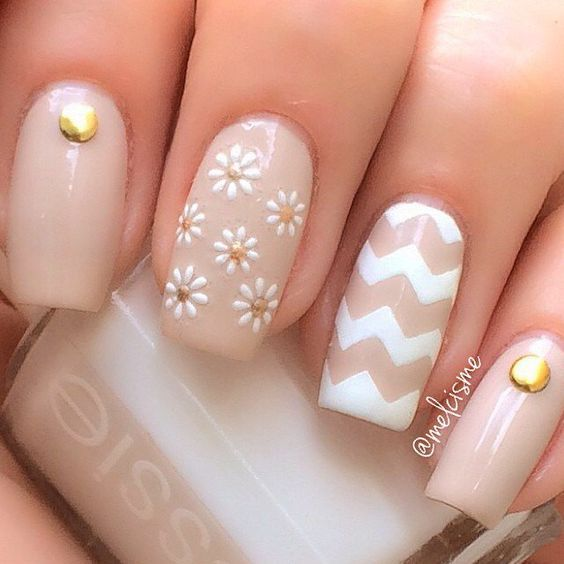 lindas uñas de color piel con colores blanco y decoración de flores blancas con el centro dorado.