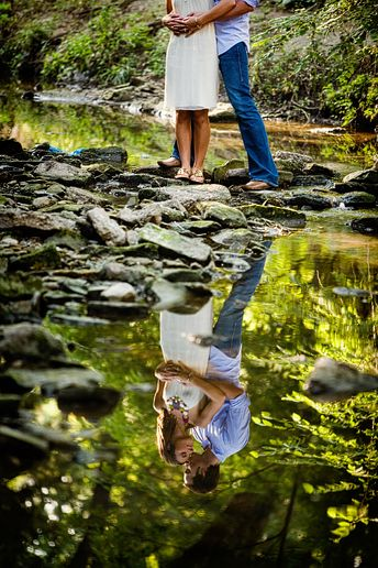 engagement portraits in a creek with a reflection at Turtle Creek Park in Highland park