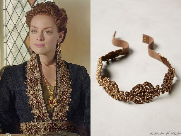 "In the episode 3x06 (""Fight or Flight"") Queen Elizabeth wears the lavish Reign Costumes Custom Black & Gold Coat Dress. The golden lace trim of Elizabeth's costume was embellished with this Anthropologie Pearl Vineyard Belt (used as an appliqué).Worn with the VSA Designs earrings."