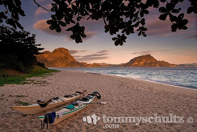Two sea kayaks on the Dilumacad Island beach in Palawan at sunset.