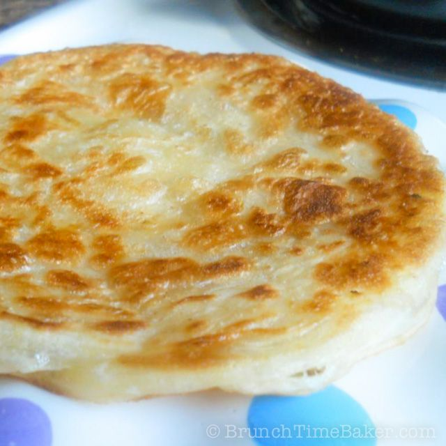 Flaky Paratha -  Crispy, delicious, Indulgent, show-stopping, perfect.  Paratha is an Indian bread that is served with just about anything. You can add honey & whipped cream or berries or chocolate and turn this into a dessert. This is the kind of breakfast that I usually make a whole bunch of and throw them in the freezer and than thaw them as needed. The dough for this recipe is similar to croissant dough but the stretching process is a bit different.
