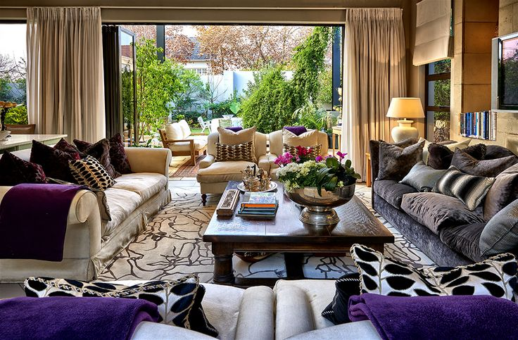 A sophisticated, stylish home in Johannesburg, showcasing a creative mixture of colours, styles and textures. Abundant use of original artworks and strong colour statements. TV room with comfortable, inviting furniture, throws and cushions.