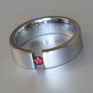 Titanium tension set ring with ruby or garnet