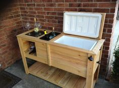 """""""Custom made wooden patio cooler with built in wine rack and wine ice bucket. Contains a new 52 qt Igloo cooler. Made from cedar wood. Granite chopping block on one side as well as ice bucket for the wine bottles. Wine bottle storage as well as wine glasses."""""""