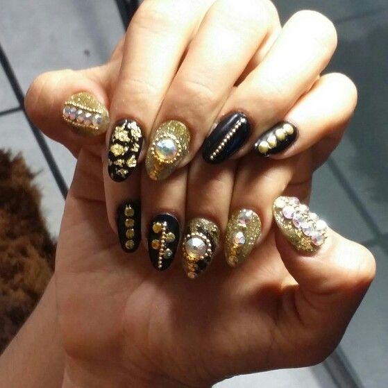 Uñas de acrílico negro dorado con piedras y hoja de oro