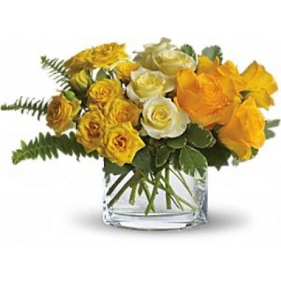 Yellow roses have a modern, tropical feel when mixed with fresh ferns and greenery in a minimalist oval vase.