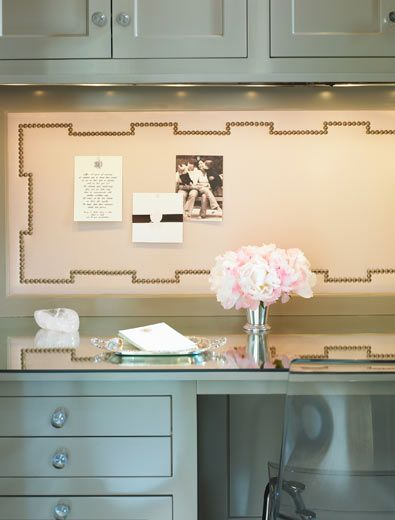 Chic small office nook design with gray green cabinets, built-in glass top desk and nailhead trim bulletin board.