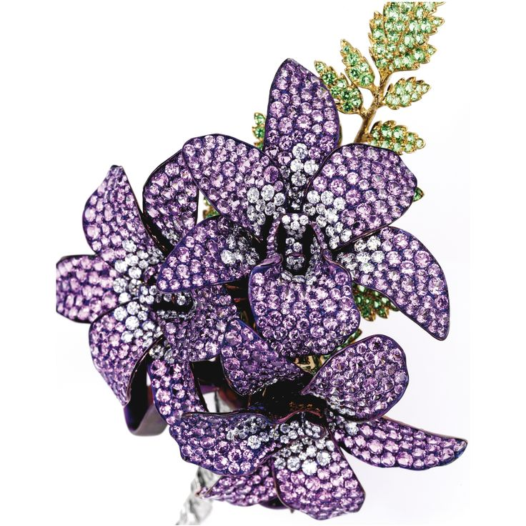18 Karat Gold, Titanium, Colored Stone and Diamond 'Boutonniere' Brooch, Michele della Valle. The fanciful arrangement of purple flowers, the petals set with round purple sapphires weighing 21.26 carats and round diamonds weighing 6.23 carats, the leaves set with round tsavorite garnets weighing 3.96 carats, gathered by a purple-hued ribbon.